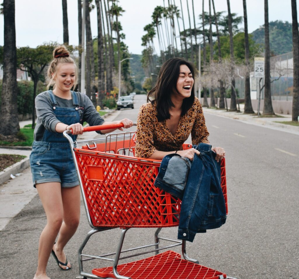 woman riding shopping cart with another woman pushing it in the middle of road